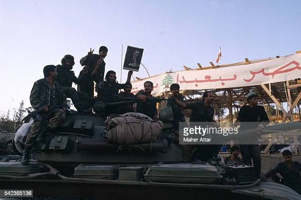 "Syrian soldiers, some doing the ""V for victory"" sign, parade through Beirut on a tank and hold up a picture of Syrian President Hafez al Assad. 