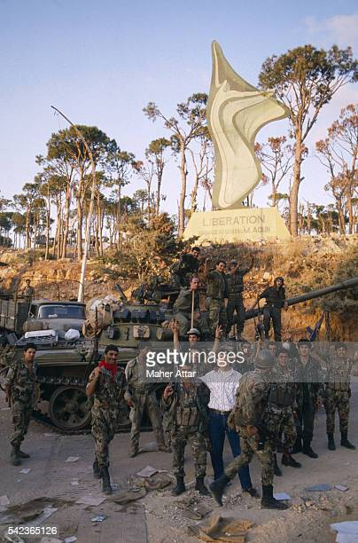 """Syrian soldiers, some doing the """"V for victory"""" sign, stand in front of a statue with their tanks, trucks and weapons around them. The statue is a..."""