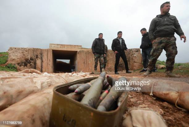 Syrian soldiers stand next to ammunition and packs they say are of C-4 explosives that were found in the southern province of Daraa on February 27...