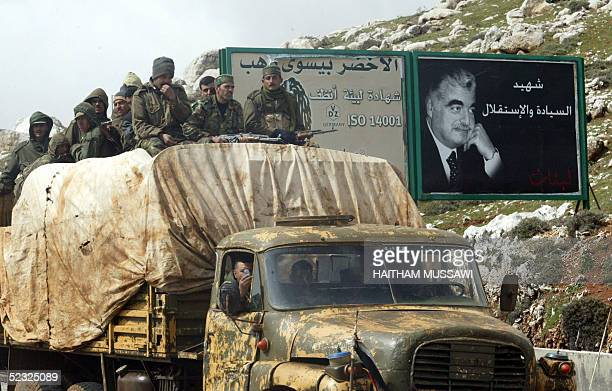 Syrian soldiers stand on the back of a military truck as they drive past a portrait of slain former Lebanese premier Rafik Hariri in Dahr alBaydar on...
