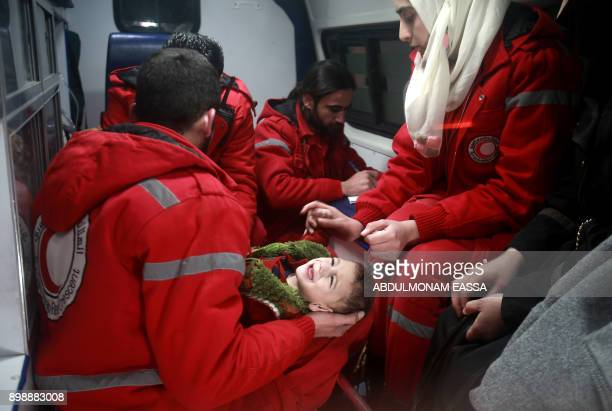 TOPSHOT Syrian staff from the International Committee of the Red Cross evacuate a baby in Douma in the eastern Ghouta region on the outskirts of the...