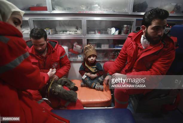 TOPSHOT Syrian staff from the International Committee of the Red Cross take part in an evacuation operation in Douma in the eastern Ghouta region on...