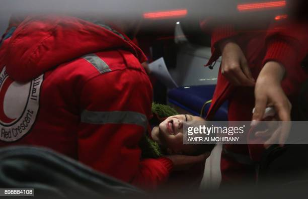Syrian staff from the International Committee of the Red Cross take part in an evacuation operation in Douma in the eastern Ghouta region on the...
