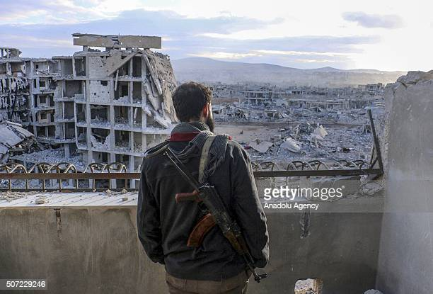 Syrian stands guard as wreckage of collapsed buildings are seen at Darayya town in Damascus Syria on January 28 2016