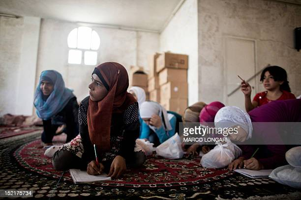 Syrian students attend classes at an improvised school in the town of Azaz on the border with Turkey on September 17 2012 Over 2000 Syrian schools...
