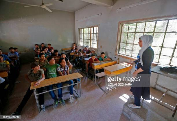 Syrian students from the former rebel held area of Eastern Ghouta attend class at a school in Kafr Batna on September 5 2018 Syrian troops recaptured...