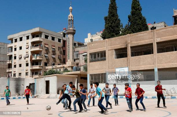 Syrian students from the former rebel held area of Eastern Ghouta play football at the courtyard of a school in Kafr Batna on September 5 2018 Syrian...