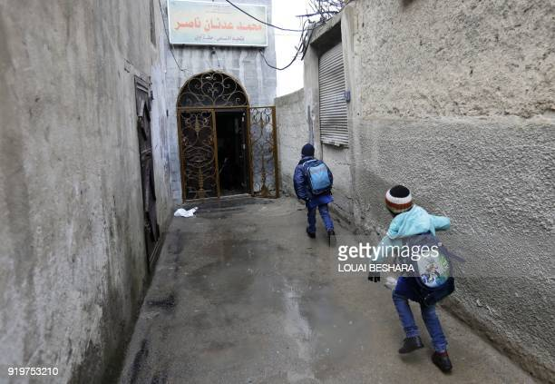 TOPSHOT Syrian students head to school on February 18 following days of calm in Damascus's Old City that has been bombarded by rebels entrenched on...
