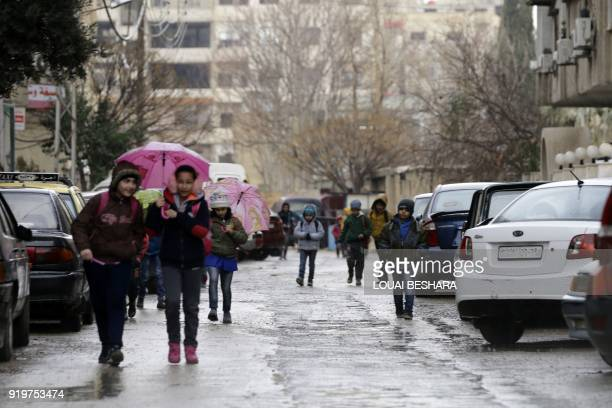 Syrian students head to school on February 18 following days of calm in Damascus's Old City that has been bombarded by rebels entrenched on the...