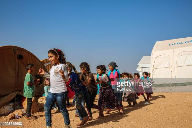 Syrian students play in front of their school tent on the first day of the new school year near the city of Maarat Misreen in Idlib countryside in...