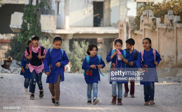 Syrian students walk on their way to school in an oppositionheld neighbourhood of the southern city of Daraa on October 2 2018