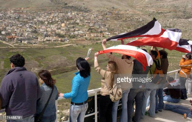 Syrian students wave national flags as they gather in Ain alTineh on the Syrian side of the Golan Heights to wish their mothers in the...