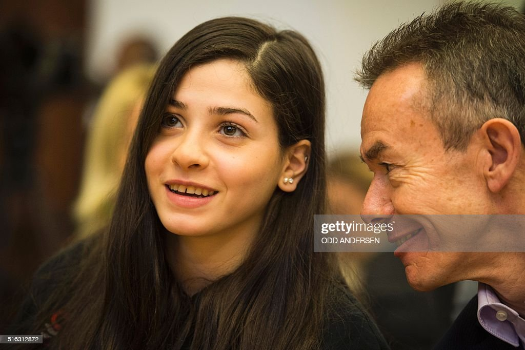 Syrian swimmer Yusra Mardini (L) and Pere Miro of the International Olympic committee (IOC) speak during a press conference in Berlin on March 18, 2016. The Syrian refugee now living in Berlin aim to qualify of the Rio2016 Olympics as part of a refugee team. / AFP / ODD