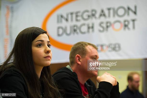 Syrian swimmer Yusra Mardini is flanked by her coach Sven Spannekrebs during a press conference in Berlin on March 18, 2016. The Syrian refugee now...