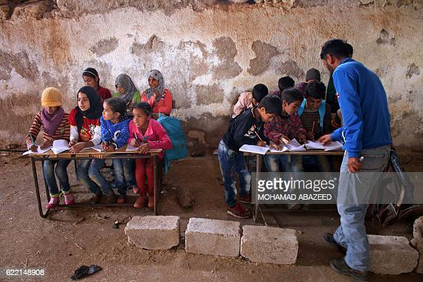 A Syrian teaches children during class in a barn that has been converted into a makeshift school to teach internally displaced children from areas...