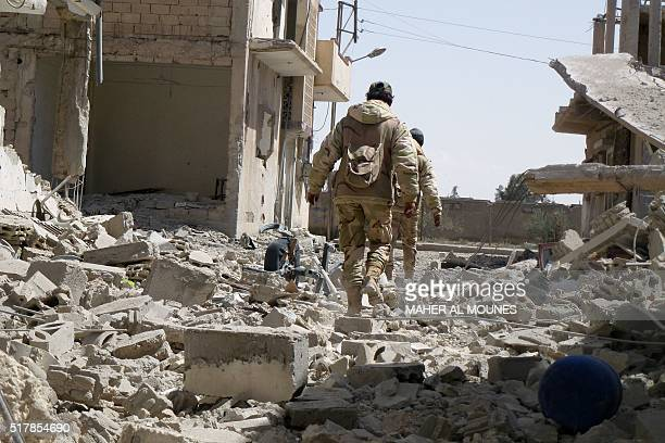 Syrian troops walk in the destroyed streets of the residential neighbourhoods in the modern town adjacent to the ancient Syrian city of Palmyra after...