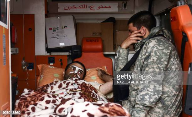 A Syrian Turkeybacked fighter sits next to an injured man in an ambulance after the latter arrived at Abu alZandin checkpoint near alBab in northern...