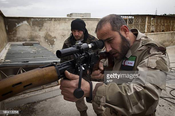 Syrian Turkmen rebel aims his weapon from the rooftop of a building in the Hanano district of the northern city of Aleppo on January 28, 2013....