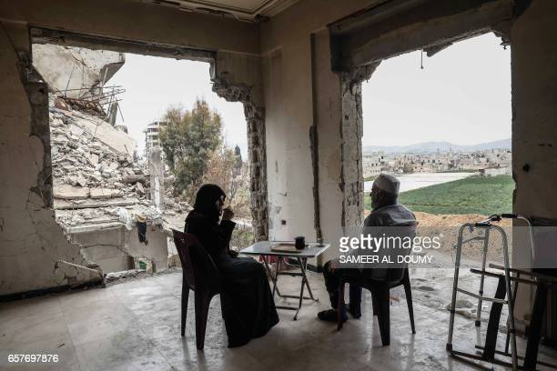 TOPSHOT Syrian Umm Mohammed and her husband drink coffee at their destroyed home in the rebelheld town of Douma on the outskirts of the capital...