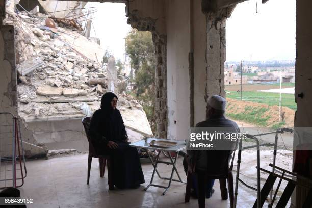 Syrian Umm Mohammed and her husband drink coffee at their destroyed home in the rebelheld town of Douma on the outskirts of the capital Damascus on...
