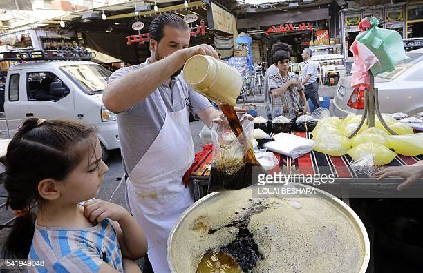 Syrian vendor pours a bag of traditional liquorice juice for a young girl in Damascus' Midan neighbourhood, which is renowned for it's sweet...