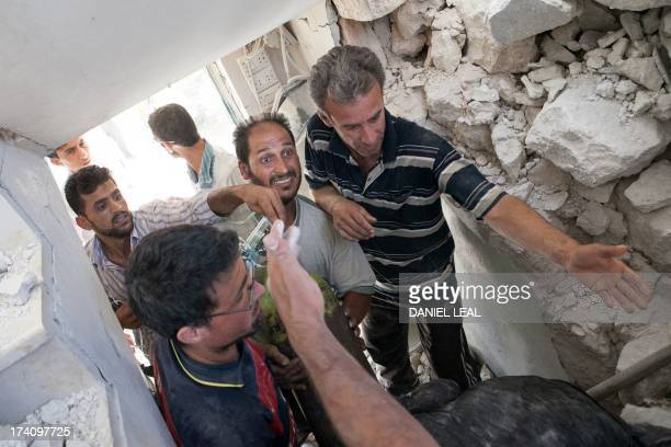 Syrian volunteers bring an oxygen tank inside a destroyed house after a barrel bomb was dropped from an air force helicopter in Saraqeb in...