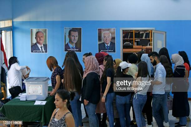 Syrian voters queue to cast their ballots at a polling station in Damascus on May 26 as voting started in government-held areas despite Western...