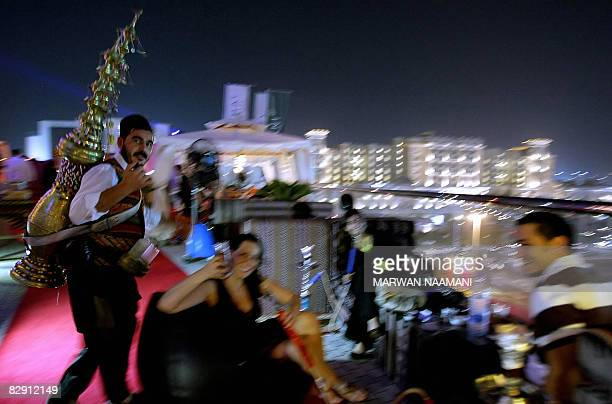Syrian waiter dressed in his country's traditional costume with a brass juice pot on his back offers drinks to clients smoking waterpipes after...