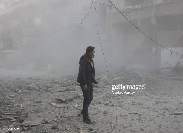 Syrian walks around debris of buildings amid dust after Assad Regime's airstrike hit residential areas in Eastern Ghouta's Douma town despite...
