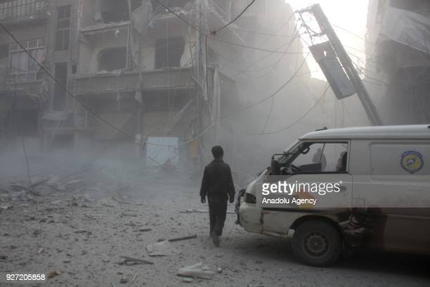 Syrian walks around near a damaged vehicle amid dust after Assad Regime's airstrike hit residential areas in Eastern Ghouta's Douma town despite...
