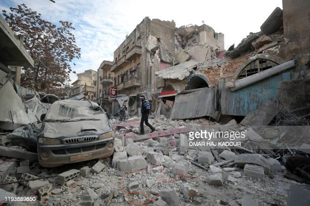 Syrian walks on the rubble of a building following a regime air strike on Ariha town in Syria's last major opposition bastion of Idlib on January 15,...