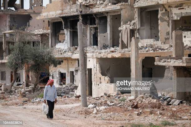 Syrian walks past the rubble of destroyed buildings in an opposition-held neighbourhood of the southern city of Daraa on October 2, 2018.