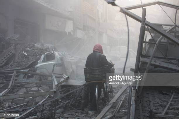 Syrian walks with his bicycle amid debris of buildings after Assad Regime's airstrike hit residential areas in Eastern Ghouta's Douma town despite...