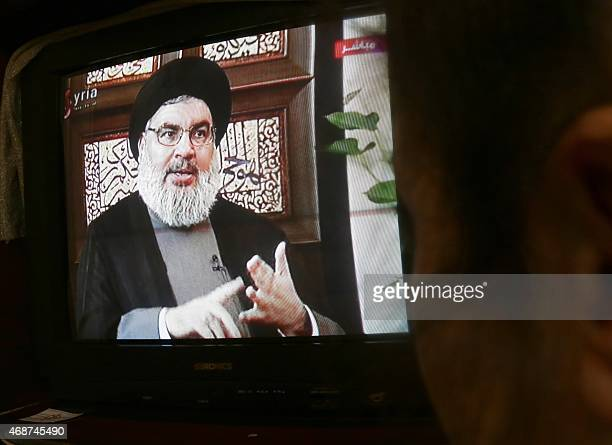A Syrian watches an interview of Hassan Nasrallah the head of Lebanon's militant Shiite Muslim movement Hezbollah screened on Syria's official...