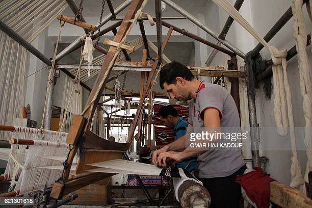 Syrian weavers Abu Mostafa and Abu Mohammad work on looms at a workshop in the village of Ariha on the southern outskirts of Syria's rebelheld Idlib...