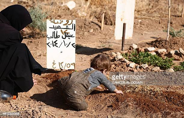 A Syrian woman and a child sit next to the grave of a relative at cemetery in the rebelheld area of Douma east of the capital Damascus on July 17 on...