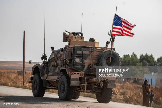 Syrian woman and a child stand on the side of a road as a US military vehicle drives on a road after US forces pulled out of their base in the...