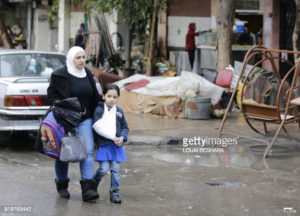 Syrian woman and a student head to school on February 18 following days of calm in Damascus's Old City that has been bombarded by rebels entrenched...