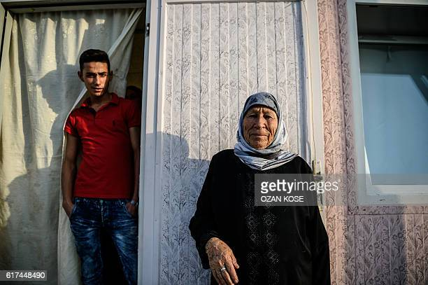 Syrian woman and a Syrian man pose at the entrance to their prefabricated home at a refugee camp in the Kilis district of Gaziantep southeastern...