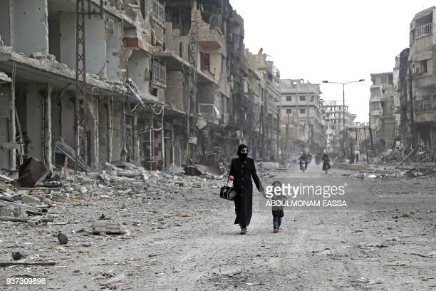 Syrian woman and child walk down a destroyed street as civilians and rebels prepare to evacuate one of the few remaining rebel-held pockets in Arbin,...