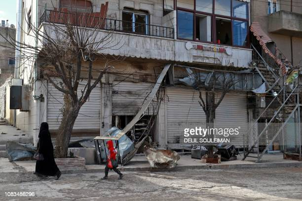 A Syrian woman and child walk past the shuttered doors of a restaurant which was the site of a suicide attack targeting USled coalition forces in the...