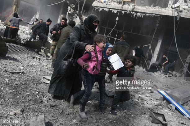 Syrian woman and children run for cover amid the rubble of buildings following government bombing in the rebelheld town of Hamouria in the besieged...