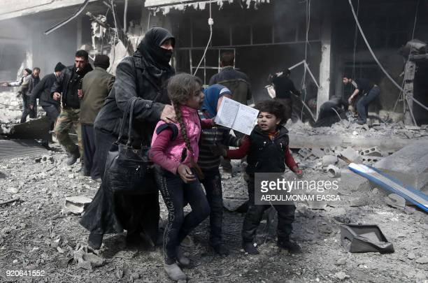 A Syrian woman and children run for cover amid the rubble of buildings following government bombing in the rebelheld town of Hamouria in the besieged...