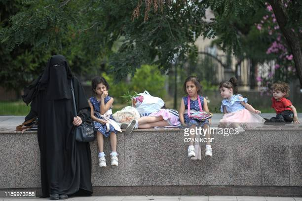 A Syrian woman and her children wait as Syrian refugees returning voluntarily to Syria prepare to board a bus on August 62019 in the Esenyurt...