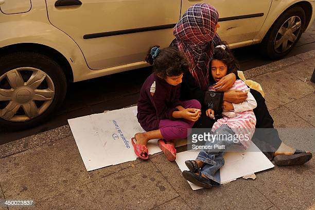 Syrian woman begs with her two children in a wealthy district of Beirut on November 16 2013 in Beirut Lebanon As the war in neighboring Syria drags...