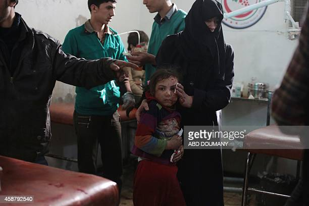 A Syrian woman brings a wounded girl for treatment at a makeshift hospital in the rebelheld Damascus suburb of Douma following a reported air strike...