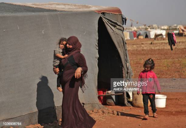 A Syrian woman carries a child as she walks past a tent at a camp for displaced civilians fleeing from advancing Syrian government forces close to a...