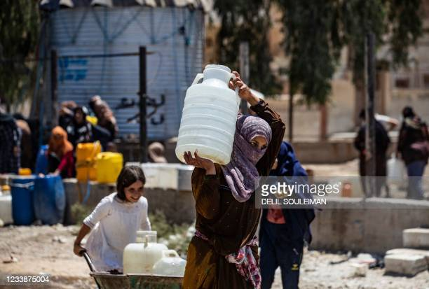 Syrian woman carries a container of water provided by the UNICEF in Syria's northeastern city of Hasakeh, on July 8 after disruption in water supply...