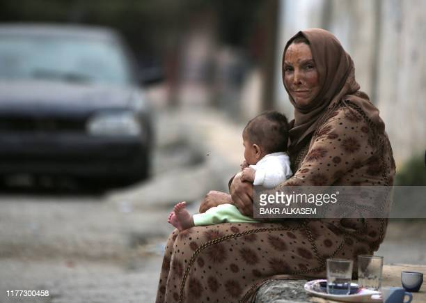 Syrian woman carries a toddler as she drinks coffee on the side of a road in the Syrian border town of Tal Abyad, seized by Turkey-backed forces last...