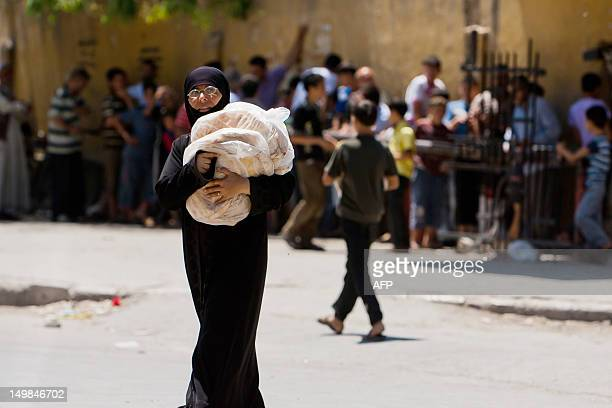 A Syrian woman carries bags of bread in the restive northern Syrian city of Aleppo on August 3 2012 Syrian regime warplanes pounded rebel positions...